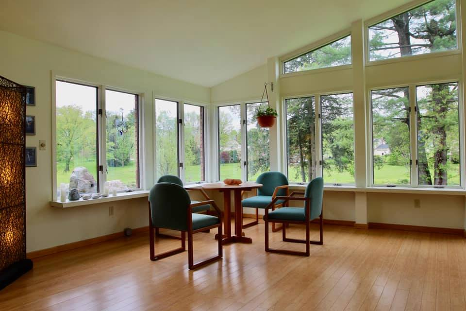 inside the center with a focus on table and chairs with the large windows showing greenery
