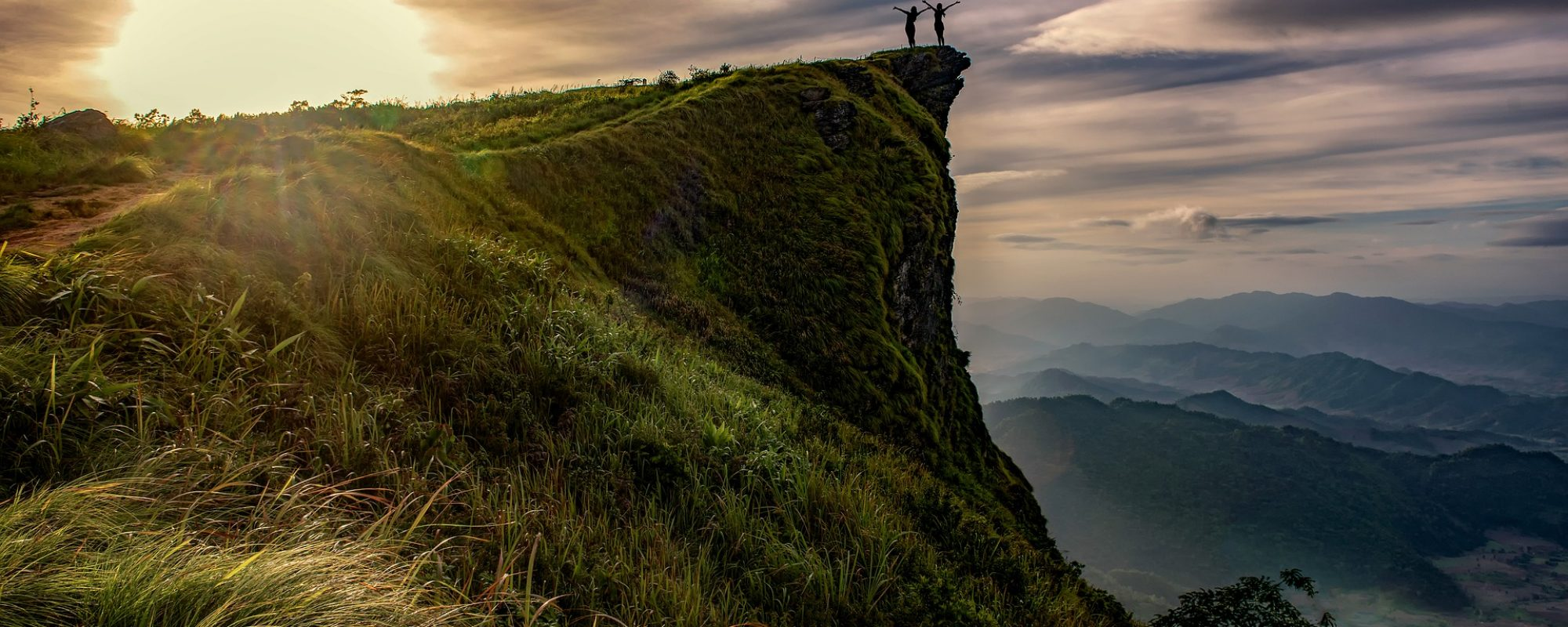 Moutain top with two people overlooking the sunset to the left, against a dark blue sky